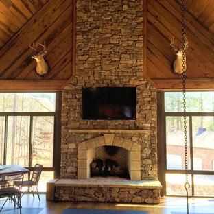 アトランタの中サイズのラスティックスタイルのおしゃれなリビングロフト (標準型暖炉、石材の暖炉まわり、壁掛け型テレビ、茶色い壁、無垢フローリング、マルチカラーの床) の写真