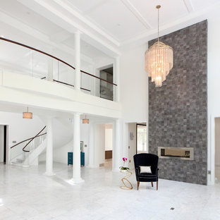 Esempio di un ampio soggiorno minimalista aperto con sala formale, pareti bianche, pavimento in marmo, camino bifacciale, cornice del camino in pietra, nessuna TV e pavimento bianco