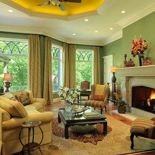 Foto di un ampio soggiorno chic aperto con sala formale, pareti verdi, pavimento in legno massello medio, camino classico e cornice del camino in pietra