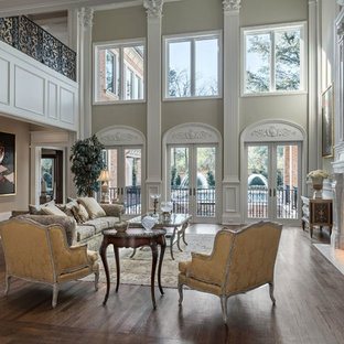 Photo of a large victorian formal enclosed living room in Dallas with beige walls, dark hardwood floors, a standard fireplace, no tv and a plaster fireplace surround.