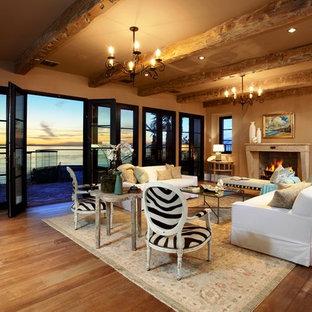 オレンジカウンティの中サイズの地中海スタイルのおしゃれなLDK (ベージュの壁、フォーマル、無垢フローリング、標準型暖炉、コンクリートの暖炉まわり、テレビなし、茶色い床) の写真