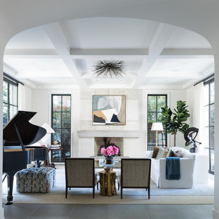 ダラスの中サイズのトラディショナルスタイルのおしゃれなLDK (ミュージックルーム、白い壁、コンクリートの床、標準型暖炉、コンクリートの暖炉まわり、テレビなし、グレーの床) の写真