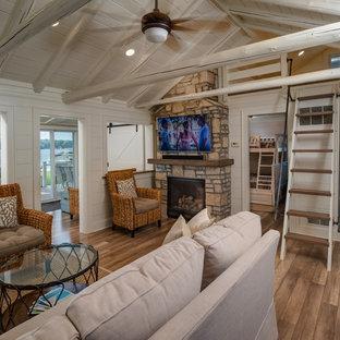 デトロイトの小さいビーチスタイルのおしゃれなリビングロフト (白い壁、淡色無垢フローリング、標準型暖炉、石材の暖炉まわり、壁掛け型テレビ、グレーの床) の写真