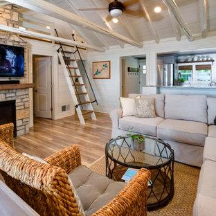 デトロイトの小さいビーチスタイルのおしゃれなリビングロフト (白い壁、淡色無垢フローリング、標準型暖炉、石材の暖炉まわり、壁掛け型テレビ、茶色い床) の写真