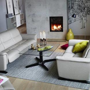 Idee per un soggiorno con pareti grigie, parquet chiaro, camino sospeso e cornice del camino in mattoni