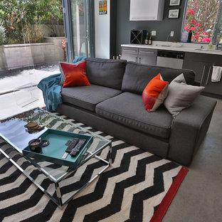 Ispirazione per un piccolo soggiorno industriale aperto con pareti bianche e pavimento in cemento