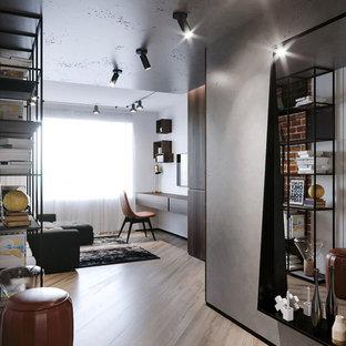 Esempio di un soggiorno industriale stile loft e di medie dimensioni con sala formale, pareti bianche, pavimento in laminato, nessun camino, TV autoportante e pavimento beige