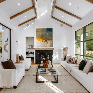Mid-sized farmhouse formal and enclosed brown floor and medium tone wood floor living room photo in Los Angeles with white walls, a standard fireplace, a stone fireplace and no tv