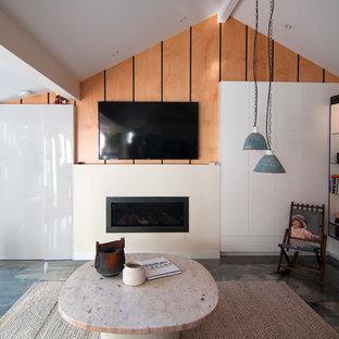 他の地域のトロピカルスタイルのおしゃれなリビングロフト (マルチカラーの壁、コンクリートの床、標準型暖炉、漆喰の暖炉まわり、壁掛け型テレビ) の写真