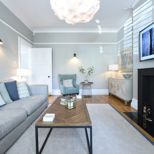 This is an example of a classic formal enclosed living room in Manchester with grey walls, medium hardwood flooring and a standard fireplace.