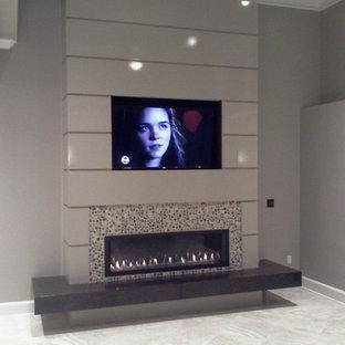 Immagine di un ampio soggiorno moderno aperto con sala formale, pareti grigie, pavimento con piastrelle in ceramica, camino sospeso, cornice del camino in pietra e parete attrezzata