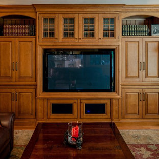 Mid-sized traditional enclosed living room in Tampa with a library, light hardwood floors, a standard fireplace, a stone fireplace surround and a built-in media wall.