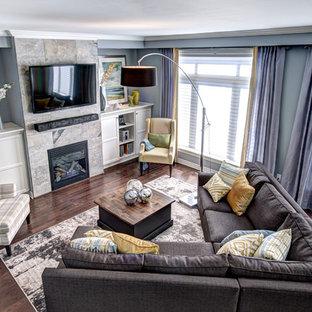 Esempio di un soggiorno minimal aperto con pareti blu, cornice del camino piastrellata e TV a parete