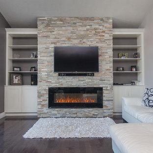 Modelo de salón para visitas abierto, contemporáneo, grande, con paredes grises, suelo de madera oscura, chimeneas suspendidas, marco de chimenea de piedra y pared multimedia