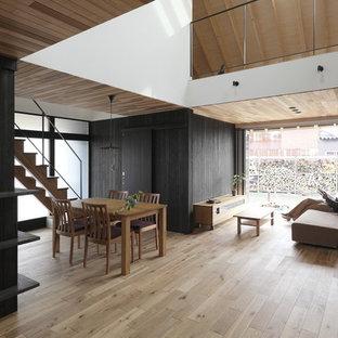 他の地域の中サイズのミッドセンチュリースタイルのおしゃれなLDK (黒い壁、無垢フローリング、壁掛け型テレビ、ベージュの床) の写真