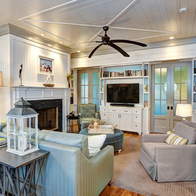 Inspiration for a mid-sized coastal open concept medium tone wood floor living room remodel in Charleston with white walls, a standard fireplace, a stone fireplace and a tv stand