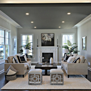 Example of a large transitional formal and enclosed dark wood floor living room design in New York with gray walls, a standard fireplace, a stone fireplace and no tv