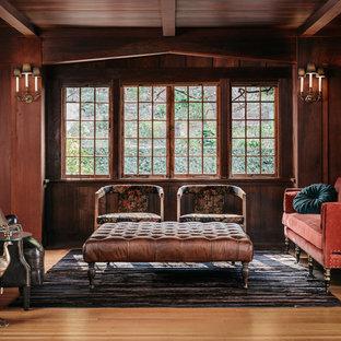 Modelo de salón para visitas tradicional con paredes marrones y suelo de madera en tonos medios