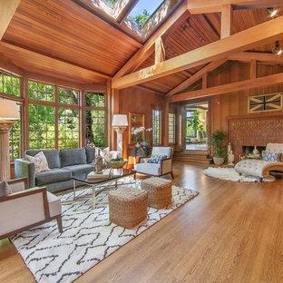 Ejemplo de salón para visitas abierto, clásico, grande, sin televisor, con suelo de madera en tonos medios, chimenea tradicional, marco de chimenea de ladrillo, paredes marrones y suelo marrón