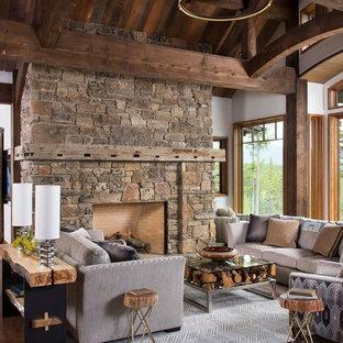 Imagen de salón para visitas abierto, rural, de tamaño medio, con paredes blancas, suelo de madera oscura, chimenea tradicional y marco de chimenea de piedra