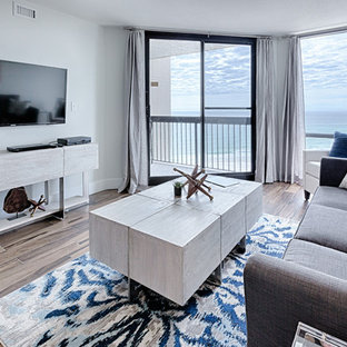 マイアミの中サイズのトラディショナルスタイルのおしゃれなLDK (フォーマル、グレーの壁、ラミネートの床、暖炉なし、壁掛け型テレビ、ベージュの床) の写真