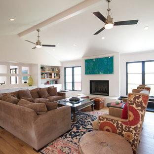Foto på ett mellanstort funkis allrum med öppen planlösning, med ett finrum, vita väggar, ljust trägolv, en standard öppen spis, en spiselkrans i gips och en dold TV