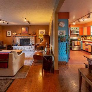 他の地域のサンタフェスタイルのおしゃれなLDK (マルチカラーの壁、標準型暖炉、石材の暖炉まわり、茶色い床) の写真