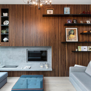 Contemporary open plan living room in London with brown walls, light hardwood flooring, no fireplace, a built-in media unit and beige floors.