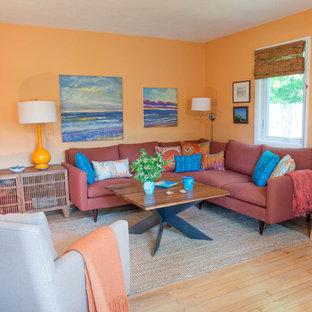 Esempio di un soggiorno design di medie dimensioni e aperto con pareti gialle, parquet chiaro, nessun camino e nessuna TV