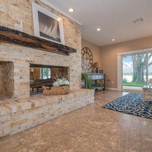 オーランドの大きいビーチスタイルのおしゃれなLDK (ベージュの壁、トラバーチンの床、両方向型暖炉、レンガの暖炉まわり、テレビなし、ベージュの床) の写真