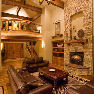 Example of a large mountain style open concept medium tone wood floor living room design in Other with beige walls, a standard fireplace, a stone fireplace and a media wall