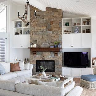 サンシャインコーストの大きいビーチスタイルのおしゃれなLDK (白い壁、無垢フローリング、標準型暖炉、石材の暖炉まわり、据え置き型テレビ) の写真