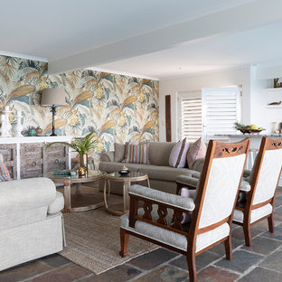 This is an example of a tropical open concept living room in Brisbane with beige walls and grey floor.