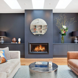 This is an example of a contemporary open concept living room in Sydney with blue walls, medium hardwood floors, brown floor, a ribbon fireplace and no tv.