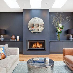Bild på ett funkis allrum med öppen planlösning, med blå väggar, mellanmörkt trägolv, brunt golv och en bred öppen spis