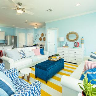 ヒューストンの中くらいのビーチスタイルのおしゃれなLDK (青い壁、ラミネートの床、暖炉なし、テレビなし、茶色い床) の写真