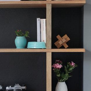 Esempio di un soggiorno design di medie dimensioni e stile loft con libreria, pareti grigie e moquette