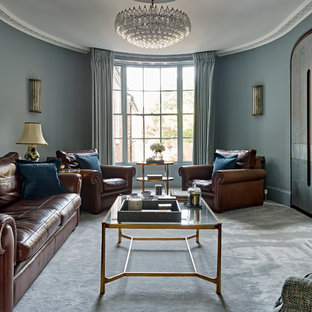 Medium sized classic enclosed living room in Sussex with carpet, a stone fireplace surround, grey floors, blue walls and a standard fireplace.