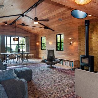 Idée de décoration pour un salon design ouvert avec un mur marron, un sol en bois brun, un poêle à bois et un sol marron.
