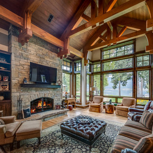 Living room - large rustic formal and enclosed light wood floor and brown floor living room idea in Other with a standard fireplace, a stone fireplace, a wall-mounted tv and beige walls