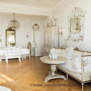 Ispirazione per un ampio soggiorno shabby-chic style aperto con pareti bianche, parquet chiaro, camino classico e cornice del camino in pietra