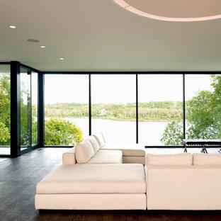 Ejemplo de salón abierto, minimalista, de tamaño medio, con suelo de cemento, paredes blancas y televisor independiente