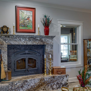 Diseño de salón para visitas abierto, de estilo americano, grande, con paredes grises, suelo de baldosas de cerámica, estufa de leña, marco de chimenea de piedra, televisor retractable y suelo gris