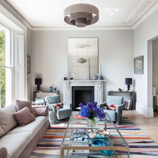 Large scandi formal enclosed living room in London with a standard fireplace, grey walls, light hardwood flooring and no tv.
