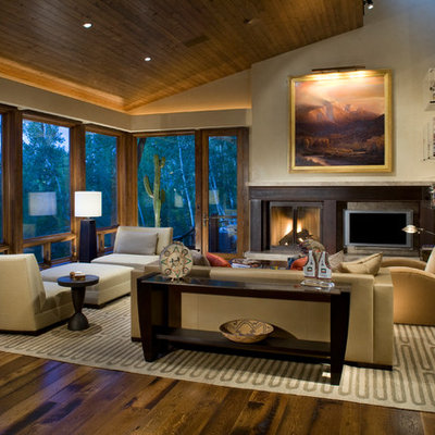 Inspiration for a mid-sized contemporary formal and enclosed medium tone wood floor and brown floor living room remodel in Denver with a standard fireplace, a wall-mounted tv, beige walls and a metal fireplace