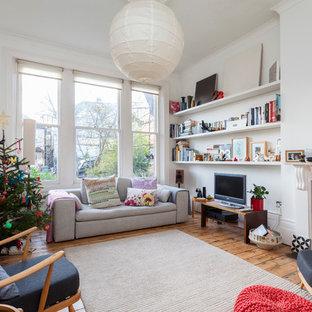 Imagen de salón bohemio con paredes blancas, suelo de madera en tonos medios, chimenea tradicional y televisor independiente