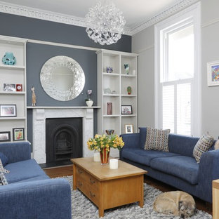 Elegant formal medium tone wood floor living room photo in Gloucestershire with a standard fireplace, a stone fireplace and gray walls