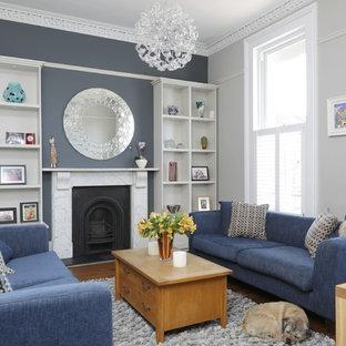 Foto di un soggiorno chic con sala formale, pavimento in legno massello medio, camino classico, cornice del camino in pietra e pareti grigie