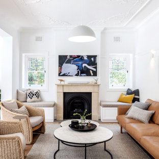 Photo of a transitional open concept living room in Sydney with white walls, medium hardwood floors, a standard fireplace and brown floor.