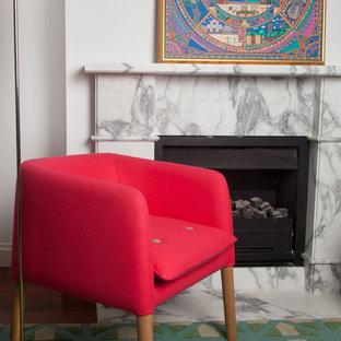Idee per un piccolo soggiorno design aperto con libreria, pareti bianche, pavimento in legno massello medio, camino classico, cornice del camino in pietra e TV autoportante